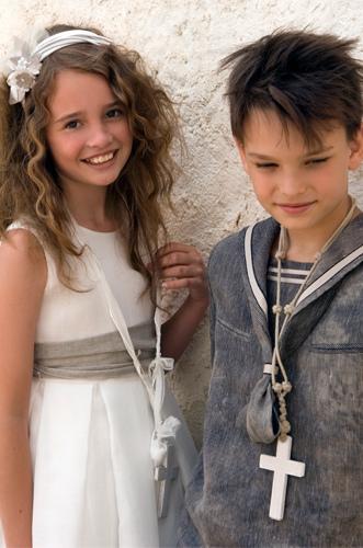 El peinado del niño despuntado y la niña lleva la melena suelta con algún rizo hecho a tenacillas y recogido con una diadema adornada